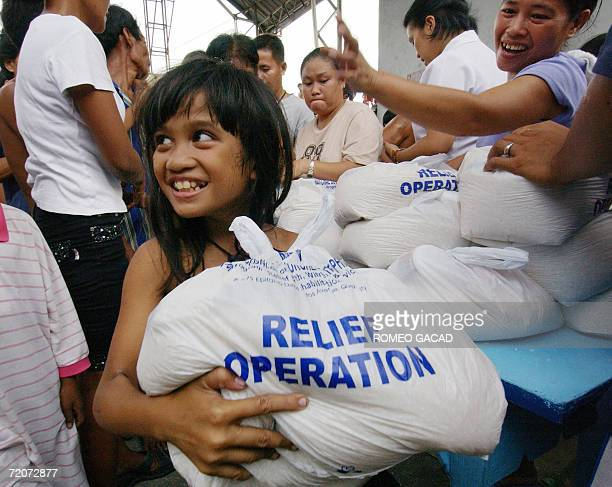 Typhoon victim Marimar Bacolod smiles after receiving bags of relief goods containing rice and canned goods from Protestant's aid National Council of...