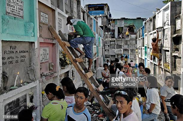 Visitors arrive at the Navotas town public cemetery in suburban Manila 01 November 2006 to honor their dead while squatter residents whose dwellings...