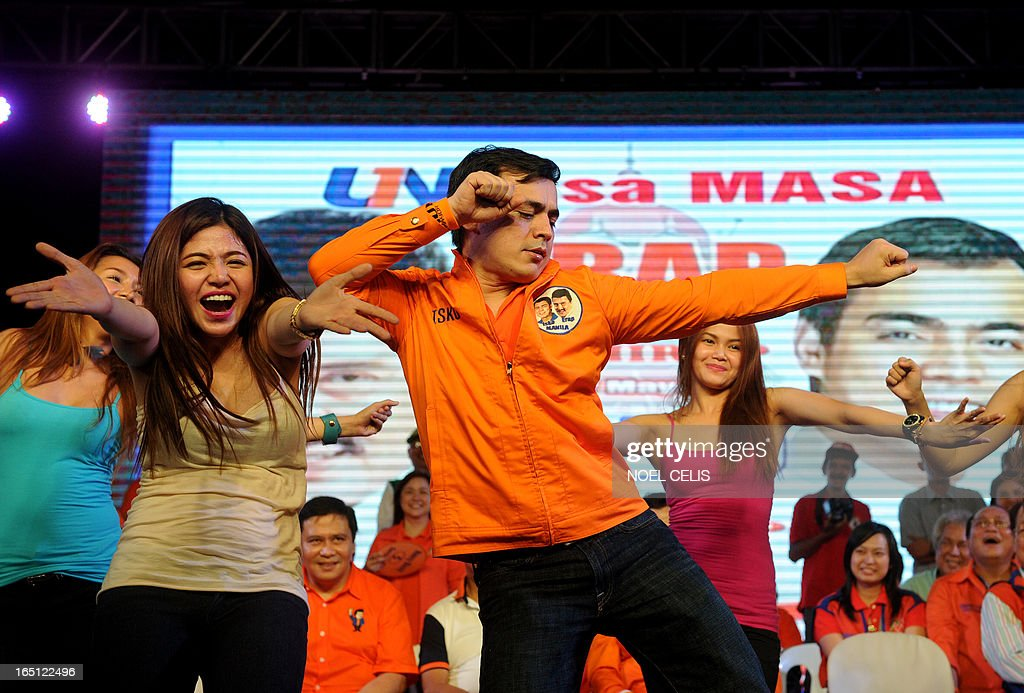 Manila's vice mayor and re-electionist Isko Moreno (C) dances with performers during former Philippine president and candidate for mayor of Manila Joseph Estrada's campaign launch on March 31, 2013 in Manila. In typically colourful fashion, graft-tainted former Philippine president Joseph Estrada launched his campaign for mayor of Manila Sunday in what he described as his 'last hurrah' in politics. The one-time movie actor, who turns 76 on April 19, said he wanted to end his political career as the mayor of a city where he was born and in whose sprawling slums he remains hugely popular. AFP PHOTO / NOEL CELIS
