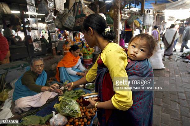 A Manipuri woman carrying a child on her back purchases goods from a vendor at the Ima Market in Imphal on November 18 2008 The Ima Market a tourist...