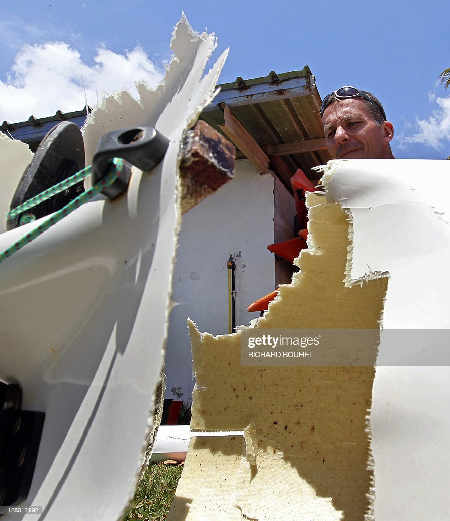 A manlooks at the pirogue damaged by a shark attack off La Houssaye cape on October 5, 2011 in Saint-Paul de la Reunion at the French overseas island of La Reunion. The kayaker, Jean-Paul Castellani was not hurt. Four shark attacks have been registered this year on the island, killing to people. Only one shark was captured during a three day track operation last September at La Reunion.