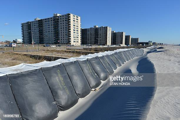 A manmade sand dune large sand bags are seen next to pilings that supported the boardwalk on the beach in the Rockaway section of the Queens borough...