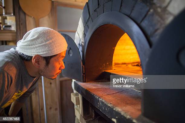 A mann checking inside a stone oven