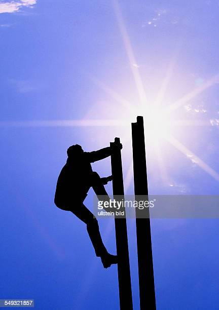 Mann klettert eine Leiter steil hinauf silhouette