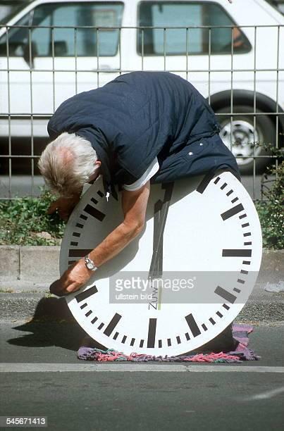 Mann putzt ein grosses Zifferblatt einer Uhr ohne Jahr