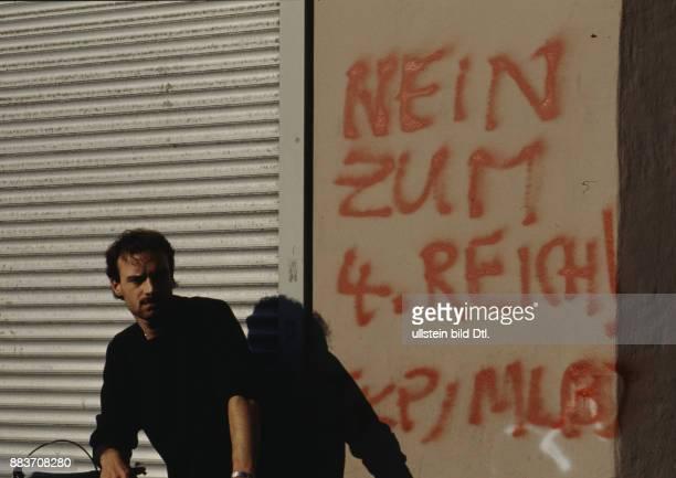 Mann sitzt vor gespraytem Graffiti NEIN ZUM 4 REICH an einer Hauswand in der Sonne