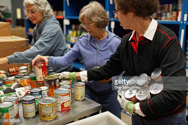 Manna Food Center volunteers Anne Engel Jan Austin and Sharon Gobel sort donated canned foods at the center November 7 2011 in Gaithersburg Maryland...