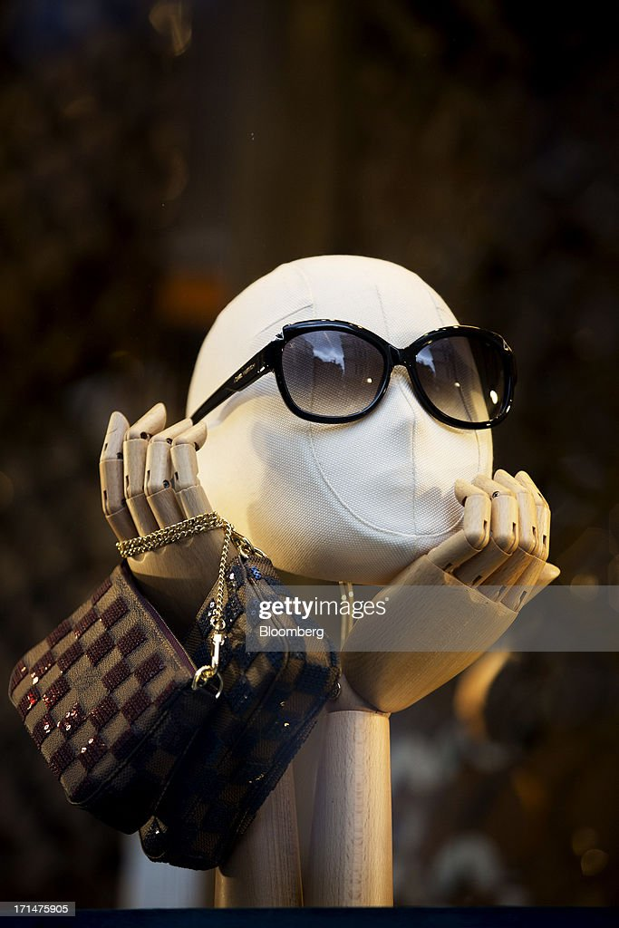 A mannequin displays sunglasses and bags on sale inside a Louis Vuitton store, operated by LVMH Moet Hennessy Louis Vuitton SA, on New Bond Street, London, U.K., on Monday, June 24, 2013. Bank of England Governor Mervyn King said the global economic recovery is at risk of further setbacks and central banks are a long way off tightening monetary policy. Photographer: Jason Alden/Bloomberg via Getty Images