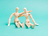 Friendly wooden mannequins hug on light blue background