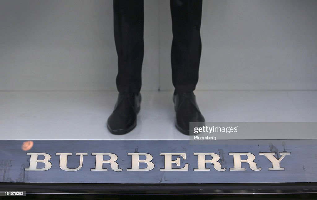 A mannequin stands beyond a logo in the window display of a Burberry Group Plc luxury clothing store on New Bond Street in London, U.K., on Tuesday, Oct. 15, 2013. Burberry named Christopher Bailey as chief executive officer to succeed Angela Ahrendts who will leave in 2014 to work as a senior vice president at Apple Inc. Photographer: Chris Ratcliffe/Bloomberg via Getty Images