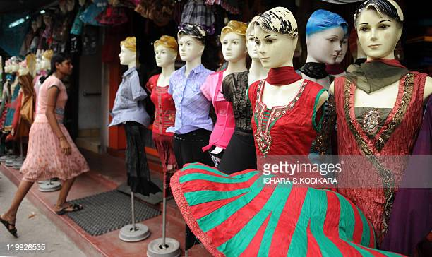 Mannequins are see on display at a roadside market as a Sri Lankan Tamil woman walks past in the northern town of Jaffna on July 27 2011 A political...