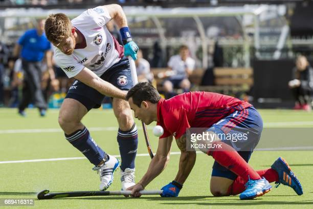 Mannheimer's Patrick Harris vies for the ball with Wimbledon's Henry Weir during the quarter final hockey match between Wimbledon and Mannheimeron...