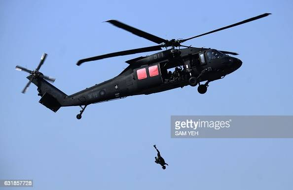 TOPSHOT A mannnequin is thrown from a USmade Black Hawk helicopter during an annual military drill in Taichung central Taiwan on January 17 2017...