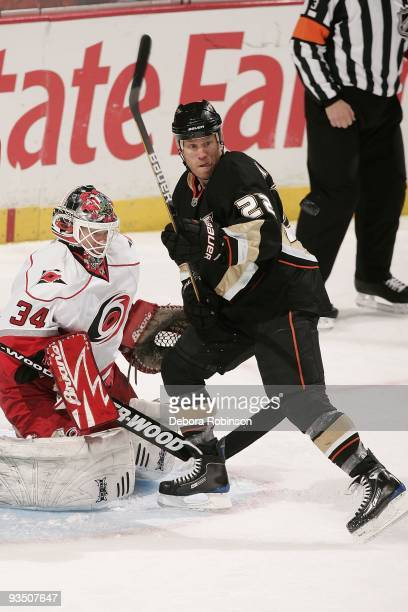 Manny Legace of the Carolina Hurricanes defends in the crease against Todd Marchant of the Anaheim Ducks during the game on November 25 2009 at Honda...