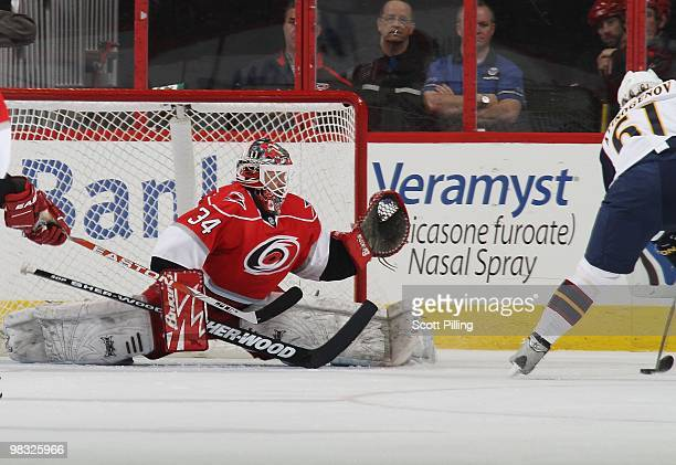 Manny Legace of the Carolina Hurricanes goes down in preparation of stopping a shot on net by Maxim Afinogenov of the Atlanta Thrashers during their...