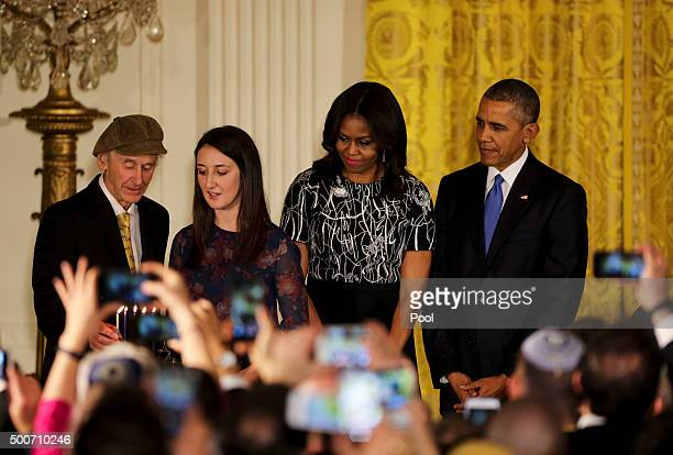 Manny Lindenbaum lights the Menorah as his granddaughter Lauren Lindenbaum first lady Michelle Obama and President Barack Obama look on during a...