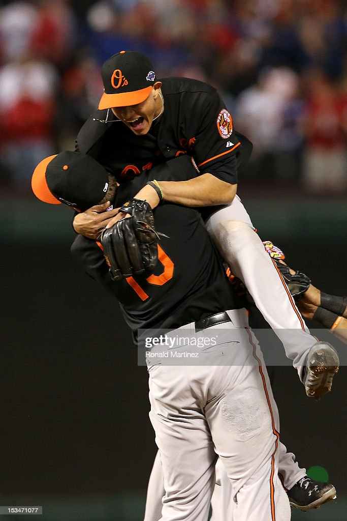 Manny Machado (R) #13 and Chris Davis (L) #19 of the Baltimore Orioles celebrate after they won 5-1 against the Texas Rangers during the American League Wild Card playoff game at Rangers Ballpark in Arlington on October 5, 2012 in Arlington, Texas.