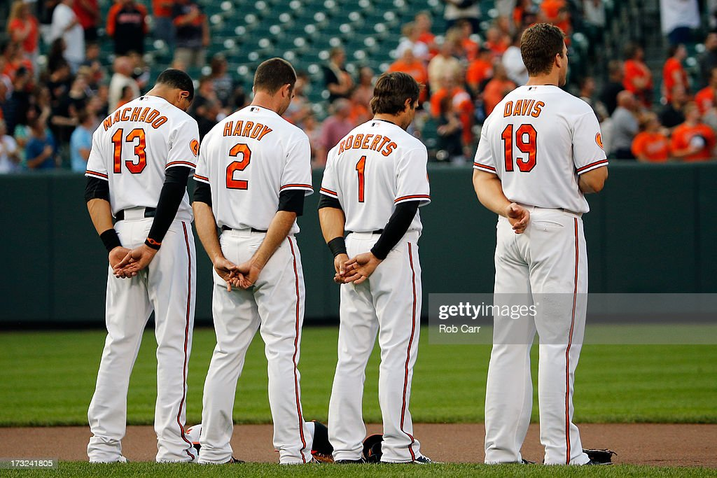 Manny Machado #13, J.J. Hardy #2, Brian Roberts #1, and Chris Davis #19 of the Baltimore Orioles stand for the national anthem before the start of the Orioles game against the Texas Rangers at Oriole Park at Camden Yards on July 10, 2013 in Baltimore, Maryland.