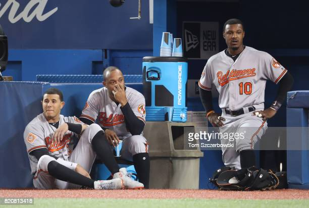 Manny Machado of the Baltimore Orioles and Jonathan Schoop and Adam Jones look on from the top step of their dugout during MLB game action against...