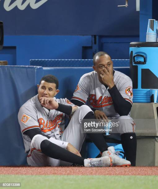 Manny Machado of the Baltimore Orioles and Jonathan Schoop look on from the top step of their dugout during MLB game action against the Toronto Blue...