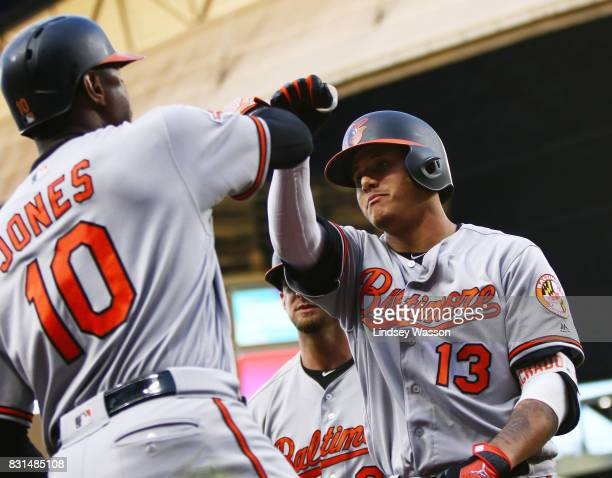 Manny Machado of the Baltimore Orioles celebrates his grand slam off of Yovani Gallardo of the Seattle Mariners with Adam Jones of the Baltimore...