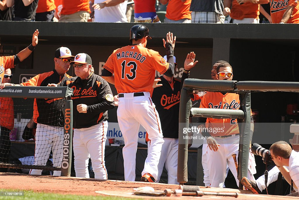 Manny Machado #13 of the Baltimore Orioles celebrates scoring teams first run in the first inning during a baseball game against the Chicago White Sox on September 7, 2013 at Oriole Park at Camden Yards in Baltimore, Maryland.