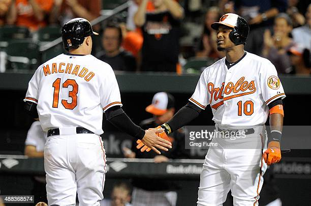 Manny Machado of the Baltimore Orioles celebrates with Adam Jones after scoring in the third inning against the Boston Red Sox at Oriole Park at...