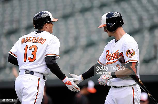 Manny Machado of the Baltimore Orioles celebrates with Caleb Joseph after scoring in the first inning against the Chicago White Sox at Oriole Park at...