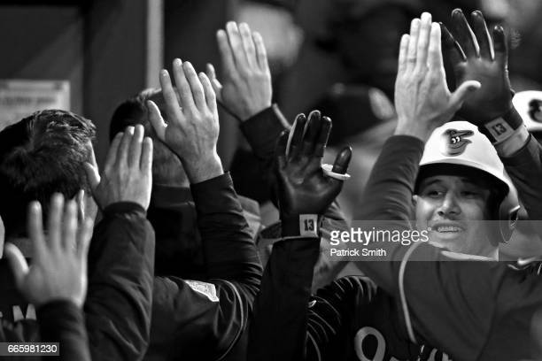 Manny Machado of the Baltimore Orioles celebrates with teammates in the dugout after hitting a three run home run against the New York Yankees during...