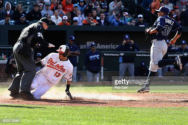 Manny Machado of the Baltimore Orioles collides with home plate umpire Dana DeMuth after scoring on a wild pitch by Erasmo Ramirez of the Tampa Bay...