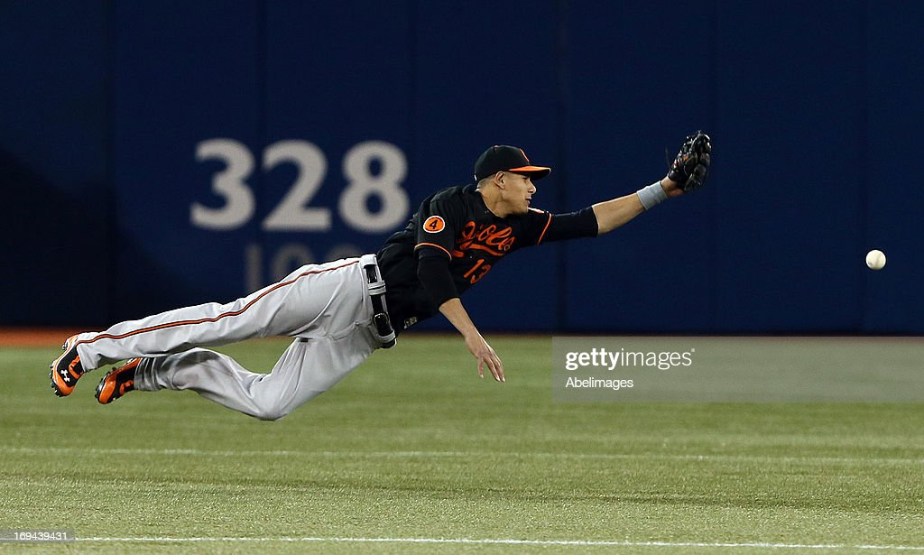 Manny Machado #13 of the Baltimore Orioles dives for a catch against the Toronto Blue Jays during MLB action at the Rogers Centre May 24, 2013 in Toronto, Ontario, Canada.