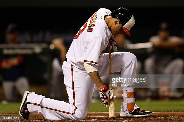 Manny Machado of the Baltimore Orioles falls after taking a swing in the third inning against the Boston Red Sox at Oriole Park at Camden Yards on...