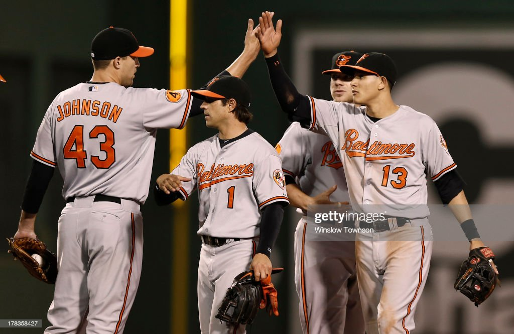 <a gi-track='captionPersonalityLinkClicked' href=/galleries/search?phrase=Manny+Machado&family=editorial&specificpeople=5591039 ng-click='$event.stopPropagation()'>Manny Machado</a> #13 of the Baltimore Orioles high fives Jim Johnson #43 of the Baltimore Orioles over Brian Roberts #1 of the Baltimore Orioles after their 3-2 win over the Boston Red Sox at Fenway Park on Aug. 29, 2013 in Boston, Massachusetts.