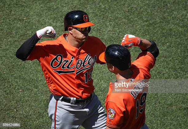 Manny Machado of the Baltimore Orioles is congratulated by Chris Davis after hitting a solo home run in the sixth inning during MLB game action...