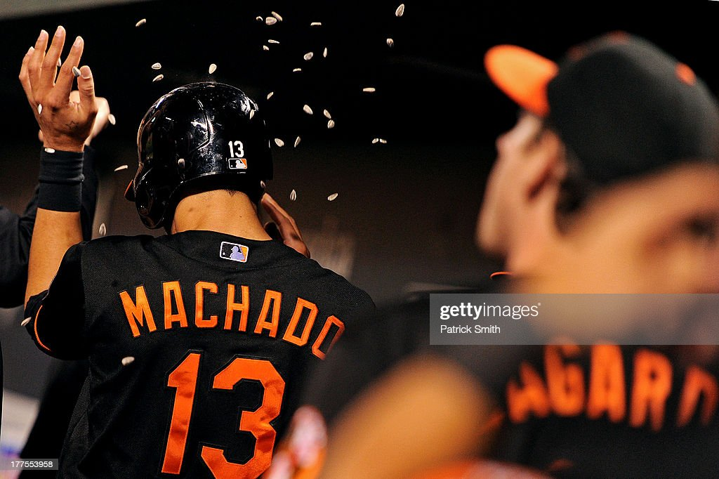 <a gi-track='captionPersonalityLinkClicked' href=/galleries/search?phrase=Manny+Machado&family=editorial&specificpeople=5591039 ng-click='$event.stopPropagation()'>Manny Machado</a> #13 of the Baltimore Orioles is greeted in the dugout after scoring off of a Adam Jones #10 (not pictured) hit in the seventh inning against the Oakland Athletics at Oriole Park at Camden Yards on August 23, 2013 in Baltimore, Maryland. The Baltimore Orioles won, 9-7.