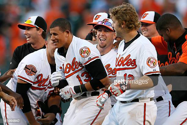 Manny Machado of the Baltimore Orioles is mobbed by teammates after driving in the winning run to give the Orioles a 32 win over the Tampa Bay Rays...