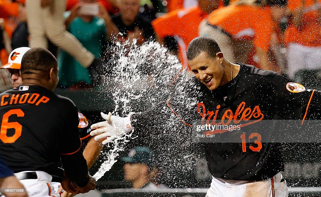 <a gi-track='captionPersonalityLinkClicked' href=/galleries/search?phrase=Manny+Machado&family=editorial&specificpeople=5591039 ng-click='$event.stopPropagation()'>Manny Machado</a> #13 of the Baltimore Orioles is sprayed with water by teammate <a gi-track='captionPersonalityLinkClicked' href=/galleries/search?phrase=Jonathan+Schoop&family=editorial&specificpeople=2526897 ng-click='$event.stopPropagation()'>Jonathan Schoop</a> #6 after hitting a two RBI walk off home run against the Oakland Athletics to give the Orioles an 8-6 win in thirteen innings at Oriole Park at Camden Yards on August 14, 2015 in Baltimore, Maryland.