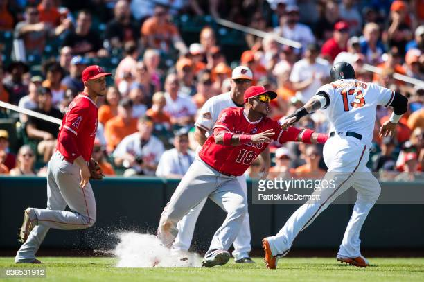 Manny Machado of the Baltimore Orioles is tagged out by Luis Valbuena of the Los Angeles Angels of Anaheim in the sixth inning during a game at...