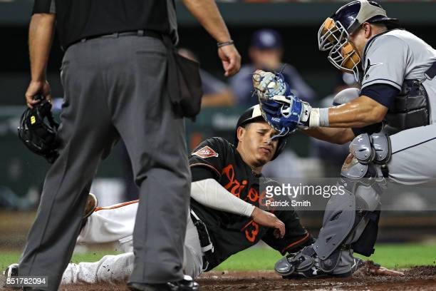 Manny Machado of the Baltimore Orioles is thrown out at home plate as he is tagged by catcher Wilson Ramos of the Tampa Bay Rays during the third...