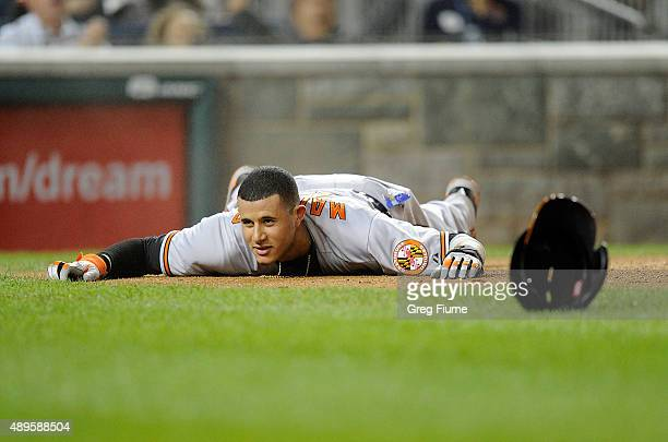 Manny Machado of the Baltimore Orioles lies on the ground after scoring in the fifth inning against the Washington Nationals at Nationals Park on...