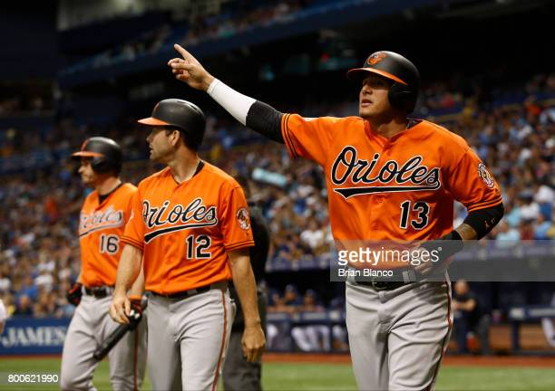 Manny Machado of the Baltimore Orioles points back to second base at Mark Trumbo after he and Seth Smith scored off Trumbo's twotun double during the...