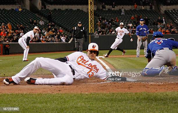 Manny Machado of the Baltimore Orioles scores a run as catcher JP Arencibia of the Toronto Blue Jays reaches for the late throw in the sixth inning...