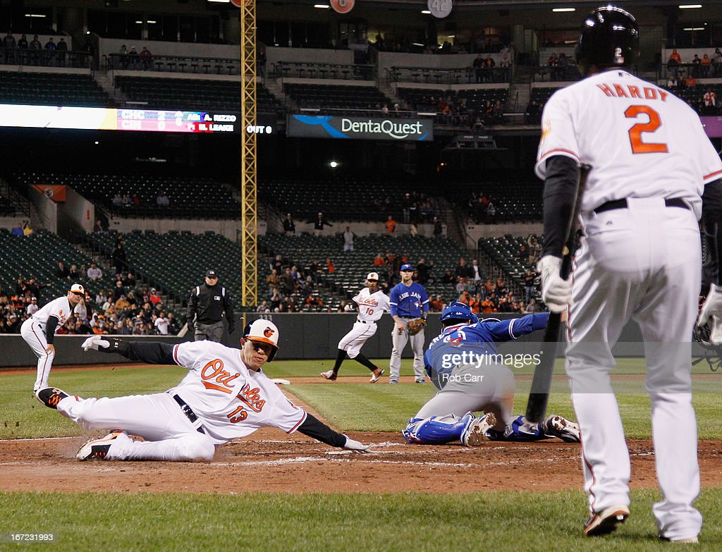 <a gi-track='captionPersonalityLinkClicked' href=/galleries/search?phrase=Manny+Machado&family=editorial&specificpeople=5591039 ng-click='$event.stopPropagation()'>Manny Machado</a> #13 of the Baltimore Orioles scores a run as catcher <a gi-track='captionPersonalityLinkClicked' href=/galleries/search?phrase=J.P.+Arencibia&family=editorial&specificpeople=4959430 ng-click='$event.stopPropagation()'>J.P. Arencibia</a> #9 of the Toronto Blue Jays reaches for the late throw in the sixth inning of the Orioles 2-1 win at Oriole Park at Camden Yards on April 22, 2013 in Baltimore, Maryland.