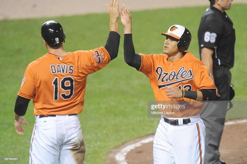 Manny Machado #13 of the Baltimore Orioles scores and celebrates with Chris Davis #19 during the seventh inning of a baseball game against the Kansas City Royals on August 12, 2012 at Oriole Park at Camden Yards in Baltimore, Maryland.