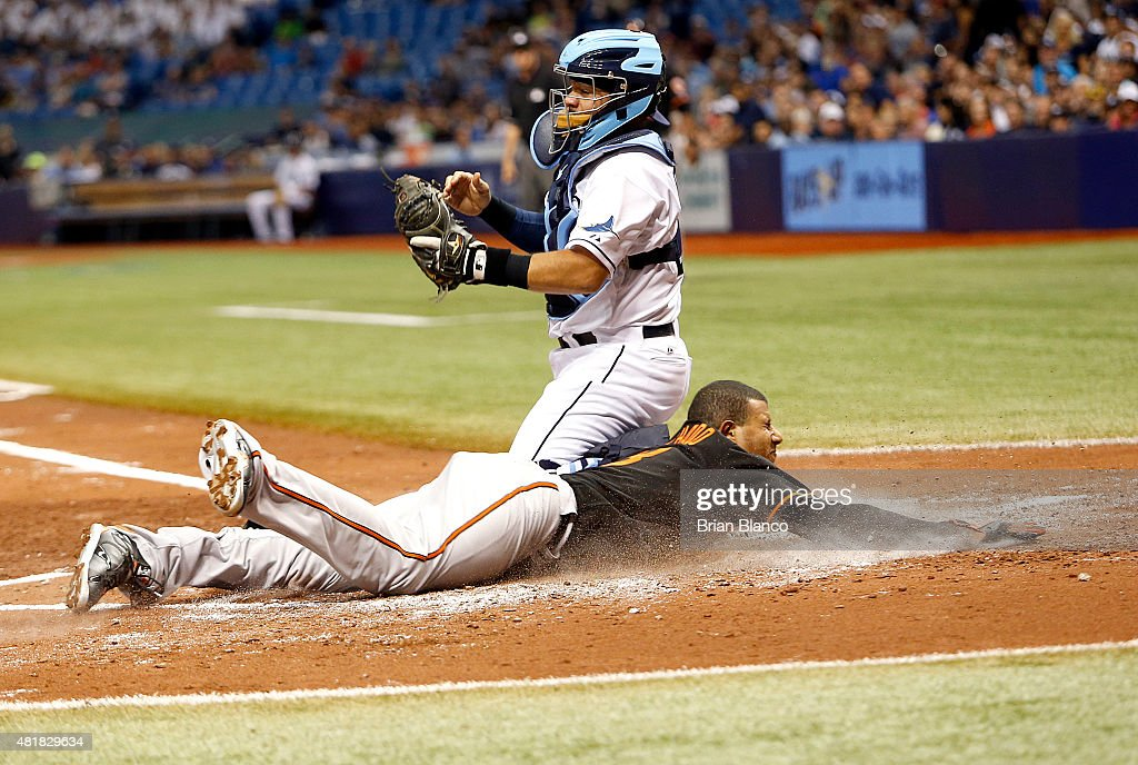 <a gi-track='captionPersonalityLinkClicked' href=/galleries/search?phrase=Manny+Machado&family=editorial&specificpeople=5591039 ng-click='$event.stopPropagation()'>Manny Machado</a> #13 of the Baltimore Orioles slides home ahead of catcher <a gi-track='captionPersonalityLinkClicked' href=/galleries/search?phrase=Rene+Rivera&family=editorial&specificpeople=234850 ng-click='$event.stopPropagation()'>Rene Rivera</a> #44 of the Tampa Bay Rays to score off of a double by Chris Davis #19 during the fourth inning of a game on July 24, 2015 at Tropicana Field in St. Petersburg, Florida.