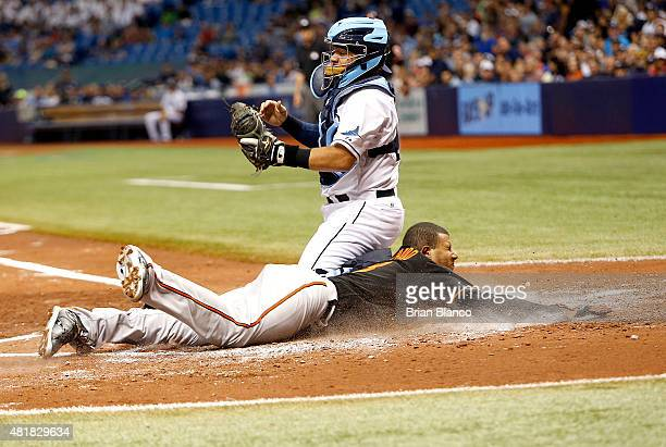 Manny Machado of the Baltimore Orioles slides home ahead of catcher Rene Rivera of the Tampa Bay Rays to score off of a double by Chris Davis during...