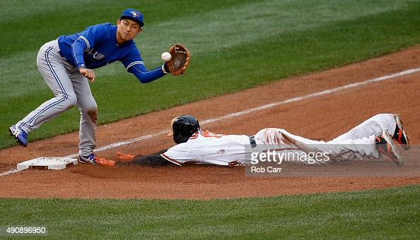 Manny Machado of the Baltimore Orioles steals third base as Munenori Kawasaki of the Toronto Blue Jays waits for the throw during the fourth inning...