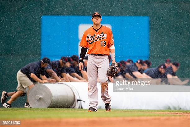 Manny Machado of the Baltimore Orioles walks off the field as the Cleveland Indians grounds crew rolls out the tarp during a rain delay in the eighth...