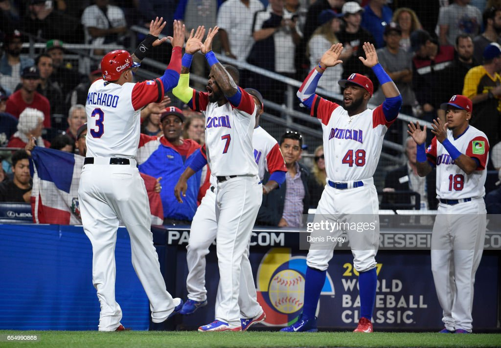 Manny Machado #3 of the Dominican Republic, left, is congratulated after scoring during the first inning of the World Baseball Classic Pool F Game Six between the United States and the Dominican Republic at PETCO Park on March 18, 2017 in San Diego, California.