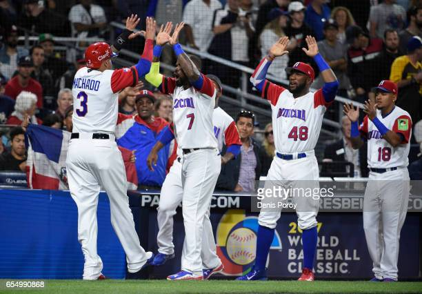 Manny Machado of the Dominican Republic left is congratulated after scoring during the first inning of the World Baseball Classic Pool F Game Six...